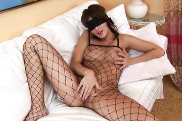 Девка в костюме с сеткой испытывает удовольствие