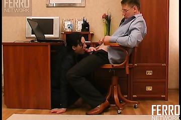 Секретарша сидя под столом, ублажает начальника минетом