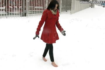 Брюнетка в красном пальто разгуливает зимой босяком